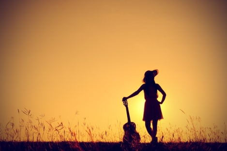 silhouette-of-woman-holding-guitar-in-sunset
